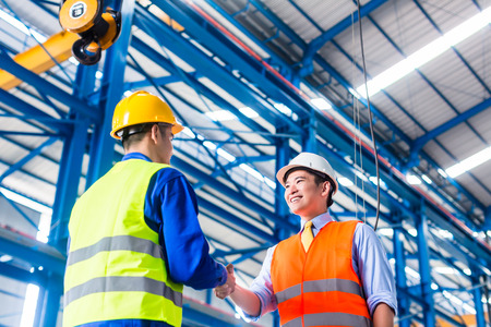 Photo pour Worker and customer having agreement in factory shaking hands - image libre de droit