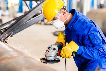 Foto de Industrial worker in manufacturing plant grinding to finish a pipeline - Imagen libre de derechos