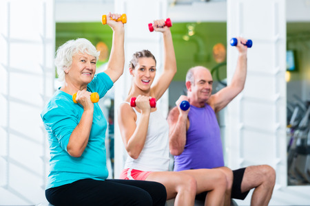 Photo pour Senior man and women with fitness trainer in gym lifting barbells as sport exercise - image libre de droit