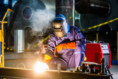 Photo for Welder working in an industrial setting manufacturing steel equipment - Royalty Free Image