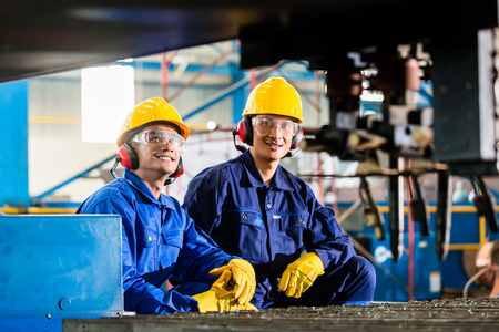 Foto de Worker in Asian factory at industrial metal cutting torch machine - Imagen libre de derechos