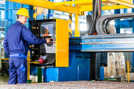 Photo pour Worker in manufacturing plant at CNC machine control panel - image libre de droit