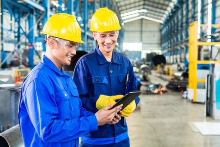 Photo for Two workers in production plant as team discussing, industrial scene in background - Royalty Free Image