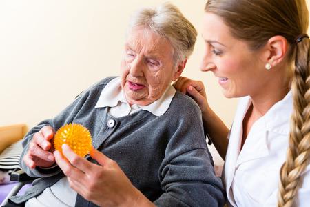 Foto de Nurse giving physical therapy with massage ball to senior woman in wheelchair - Imagen libre de derechos