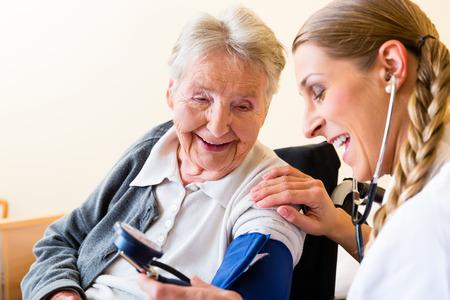 Foto de Nurse measuring blood pressure at senior woman patient in retirement home - Imagen libre de derechos