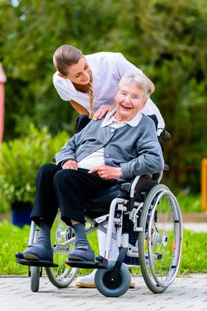 Foto de Nurse pushing senior woman in wheelchair on walk thru garden in summer - Imagen libre de derechos