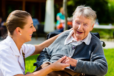 Foto de Nurse holding hands with senior woman sitting in wheelchair in garden of retirement home - Imagen libre de derechos