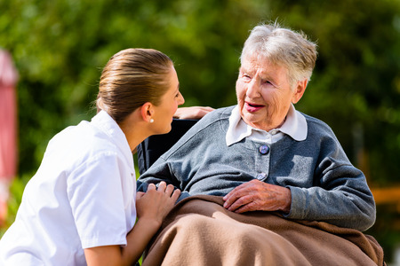 Photo for Nurse holding hands with senior woman sitting in wheelchair in garden of retirement home - Royalty Free Image