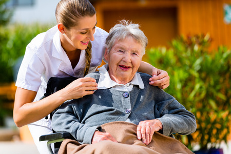 Photo for Senior woman in nursing home with nurse in garden sitting in wheelchair - Royalty Free Image
