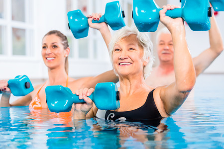 Foto de People young and senior in water gymnastics physiotherapy with dumbbells - Imagen libre de derechos