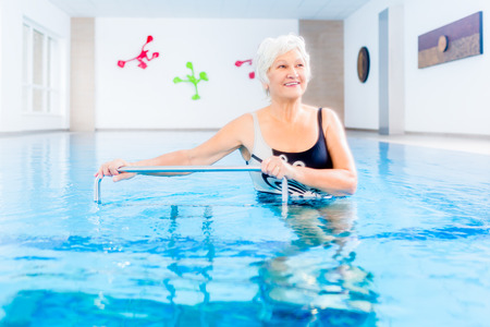 Photo pour Senior woman in underwater gymnastics therapy with sliding machine - image libre de droit