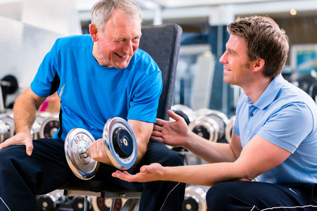 Foto de Senior man and trainer at exercise in gym with dumbbell weights - Imagen libre de derechos