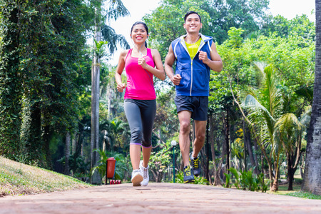 Photo pour Asian couple, man and woman, jogging or running in tropical Asian park for fitness - image libre de droit