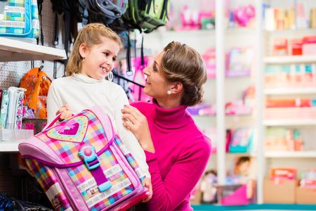 Foto de Mother and kid becoming a student buying school satchel or bag in store - Imagen libre de derechos