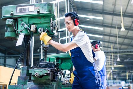 Foto de Asian worker in production plant drilling at machine on the factory floor - Imagen libre de derechos