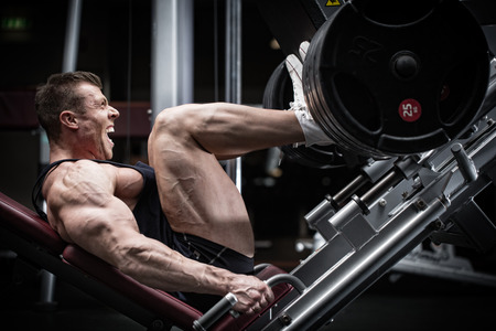 Foto de Man in gym training at leg press to define his upper leg muscles - Imagen libre de derechos