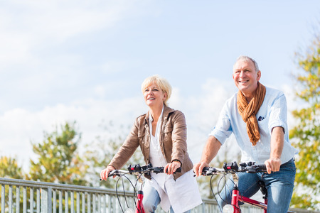 Photo for Senior couple, married woman and man, riding their bicycles over a bridge enjoying some leisure time - Royalty Free Image