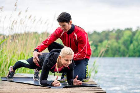 Foto de Woman with personal trainer doing fitness push-up - Imagen libre de derechos
