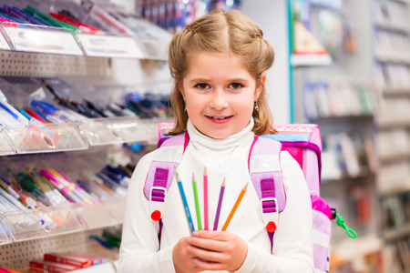Photo pour Student in stationery store buying pens holding them into the camera - image libre de droit