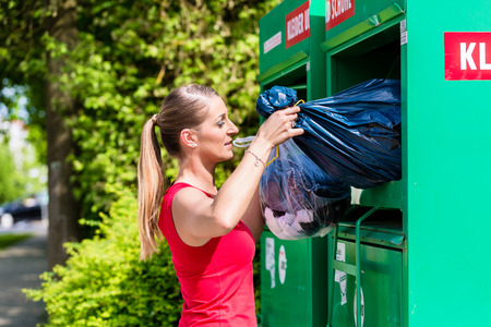 Photo for Woman at clothes recycling skip - Royalty Free Image