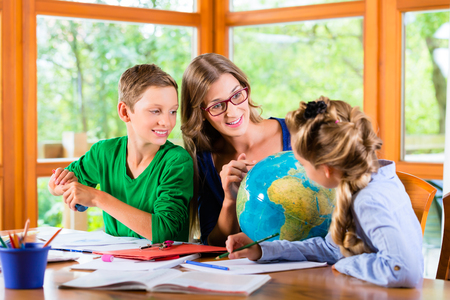 Foto de Homeschooling mother teaching kids private lessons in geography - Imagen libre de derechos