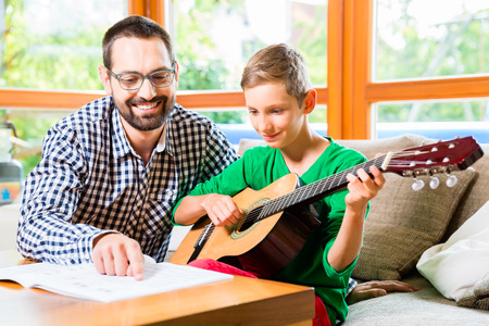 Foto de Father and son playing guitar at home, making music together - Imagen libre de derechos