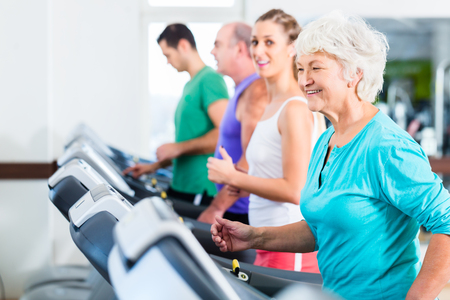 Foto per Group with senior and young men and women on treadmill in fitness gym running for sport - Immagine Royalty Free