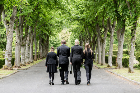 Photo pour Family walking down alley at graveyard - image libre de droit