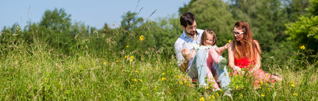 Photo pour Panorama picture of family with mom, dad and daughter on meadow - image libre de droit