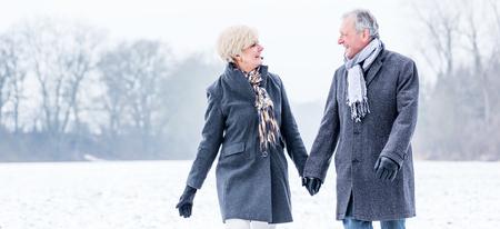Photo pour Senior couple having walk in winter - image libre de droit
