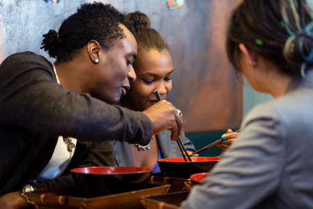 Photo pour Friends, black and Latin people, eating ramen noodle soup in Japanese Restaurant - image libre de droit
