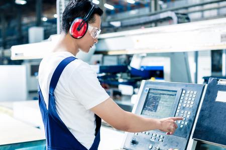 Foto de Worker entering data in CNC machine at factory floor to get the production going - Imagen libre de derechos