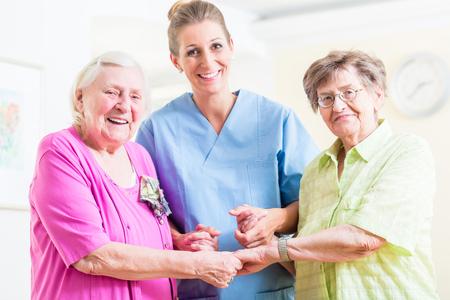 Foto de Elderly care nurse with two senior women - Imagen libre de derechos