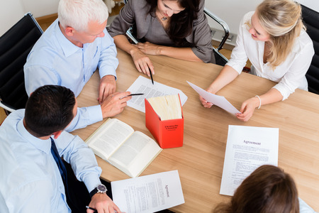 Photo for Lawyers in law firm reading documents and agreements at large conference table - Royalty Free Image