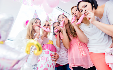 Foto de Group of women on baby shower party having fun wearing party hats blowing paper streamer - Imagen libre de derechos
