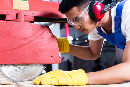 Photo pour Carpenter in Asian workshop with circular saw in a manufacturing factory - image libre de droit