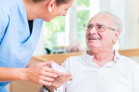 Foto per Nurse giving senior man prescription drugs - Immagine Royalty Free