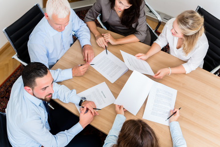 Photo pour Lawyers having team meeting in law firm reading documents and negotiating agreements - image libre de droit