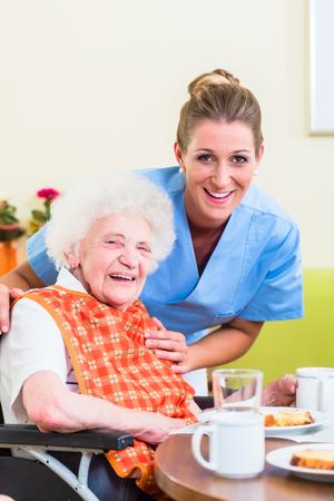 Foto de Nurse with senior woman helping with meal - Imagen libre de derechos