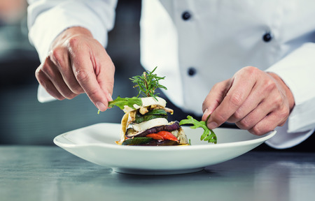 Foto de Chef in Restaurant garnishing vegetable dish, crop on hands, filtered image - Imagen libre de derechos