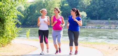 Photo pour Group of women running at lakeside jogging - image libre de droit