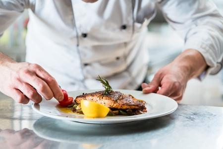 Foto de Chef with diligence finishing dish on plate, fish with vegetables - Imagen libre de derechos