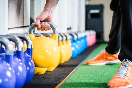 Photo for Man lifting kettlebell from floor doing sport in gym - Royalty Free Image