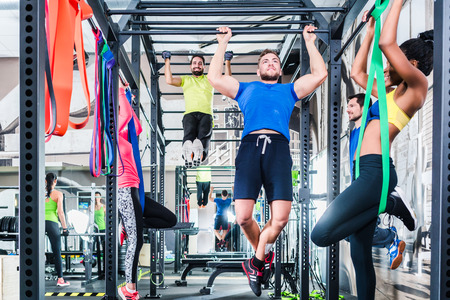 Photo pour Group of women and men in cage at fitness sport exercise in gym - image libre de droit