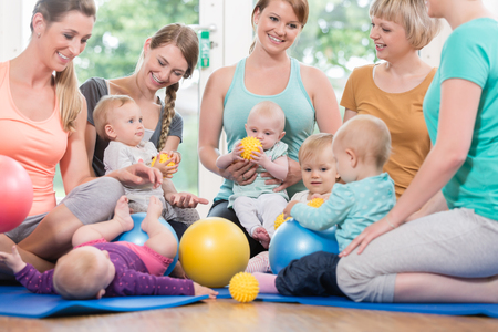 Photo for Young women in mother and child group playing with their baby kids - Royalty Free Image