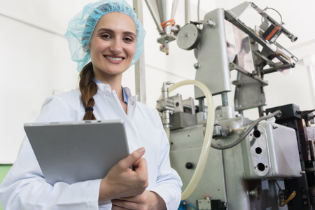 Foto de Portrait of a quality control female inspector smiling and looking at camera while holding a tablet during inspection in a contemporary cosmetics factory - Imagen libre de derechos