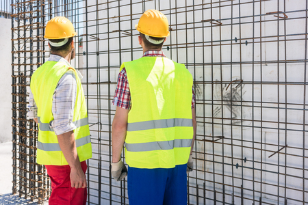 Foto de Two blue-collar workers wearing safety equipment, while checking the durability of the steel structure for the reinforcement of the walls of a building under construction - Imagen libre de derechos