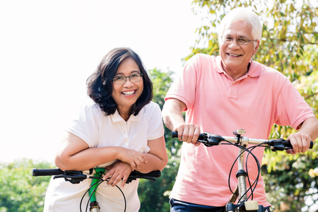 Photo for Portrait of active senior couple smiling while standing on bicycles outdoors in summer - Royalty Free Image