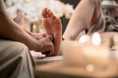 Photo pour Woman enjoyingreflexology foot massage in wellness spa - image libre de droit