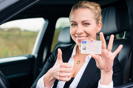 Photo for Woman showing driving license and thumbs up - Royalty Free Image